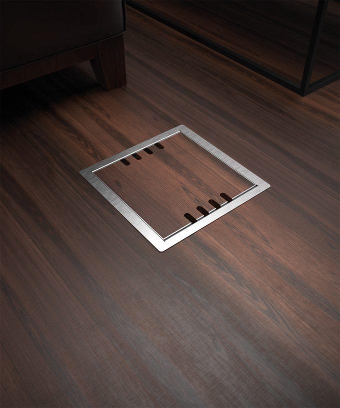 Hohlbodentank 8508B mit 8 Schuko-Steckdosen bestückt im Holzboden eingebaut Deckel geschlossen mit Bodenbelag und Kabelauslass