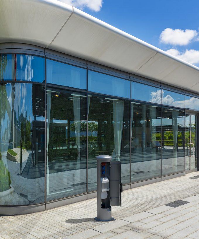 Energiesäule Energiepolle ESP14 mit offener Tür vor einem Gebäude am Parkplatz